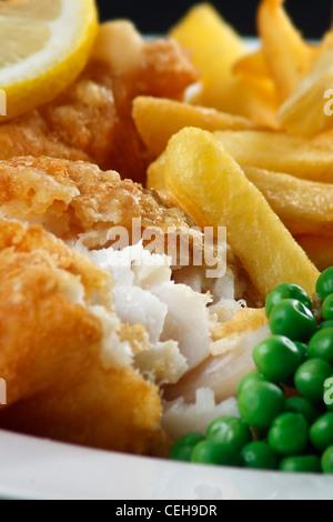 Nahaufnahme von Fish And Chips mit Erbsen und einer Scheibe Zitrone. Ein traditionelles Gericht der britischen Küste - Stockfoto