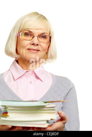 Schöne Reife Dame hält einen Stapel Notizbücher Bücher und lächelt in die Kamera - Stockfoto