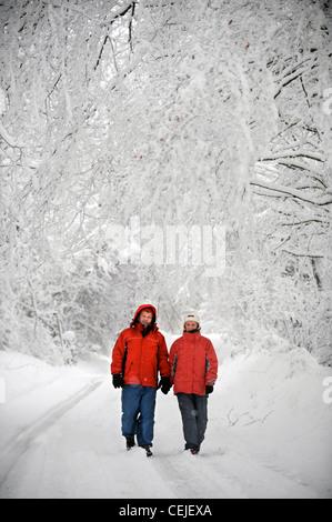 Ein paar in passenden roten Wintermäntel zu Fuß in einer Cotswold-Gasse in Schneeverhältnissen UK - Stockfoto