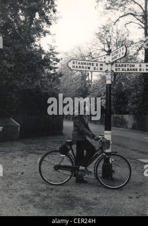 Archivfoto: Frau auf einem Fahrrad in der Nähe von Wegweiser (c1945) - Stockfoto