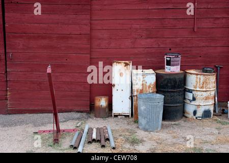Außenseite des roten Scheune mit Stahl Fässer gestapelt daneben - Stockfoto