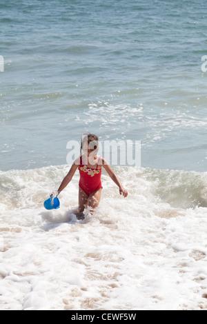 Begeistert kleine Mädchen laufen in der Meeresbrandung mit einem blauen Eimer - Stockfoto
