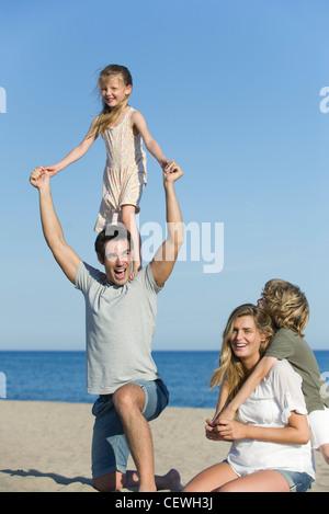 Familie zusammen am Strand, spielen Mädchen steht auf Vaters Schultern - Stockfoto