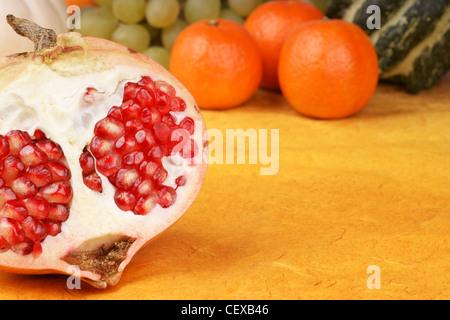 In Scheiben geschnitten Granatapfel auf gelb-braunen Hintergrund. Clementinen, Traube und dekorative Kürbisse im - Stockfoto