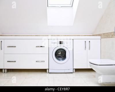Modernes Badezimmer mit glänzenden weißen Schränke und Waschmaschine - Stockfoto