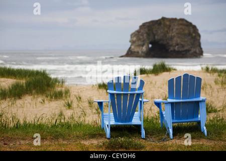 zwei blaue Adirondack Stühle auf einem grasbewachsenen Strand mit Felsformationen im Meer; Rockaway beach Oregon - Stockfoto