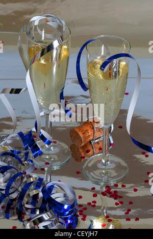Zwei Gläser Champagner auf einer reflektierenden Oberfläche, umgeben von metallischen blauen und silbernen Luftschlangen, - Stockfoto