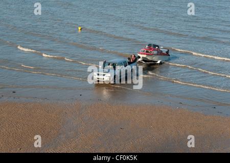 Ein 4 x 4 in einem Boot zu bringen, da die Flut bei The Mumbles, Wales kommt - Stockfoto