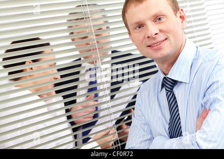 Porträt eines zuversichtlich Geschäftsmann, Blick in die Kamera, während seine Kollegen haben eine Diskussion im - Stockfoto