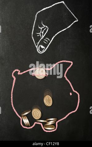 Kreide gezeichnete Hand fallenlassen echten Pfund Münzen in einem Chalk piggy Bank gezogen - Stockfoto