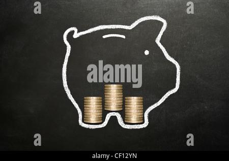 Sparschwein mit Kreide auf einer Tafel mit 3 Stapel von echten Münzen ausgehen. - Stockfoto