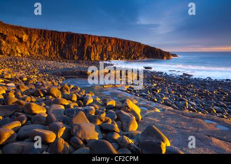 Dawn Licht erhellt die felsige Küste der Cullernose Punkt, in der Nähe von Dorf Craster an der Northumberland-Erbe - Stockfoto