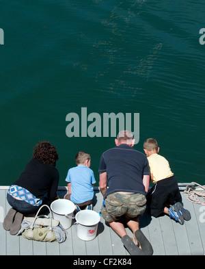 Eine Familie, kniend auf eine Anlegesteg Fischerei Krebse in Falmouth. - Stockfoto