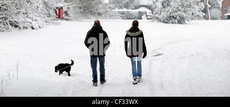 Wandern im Schnee entlang der Landstraße Paar morgen Hund zu Fuß nach starker Schneefall Brentwood Essex England - Stockfoto