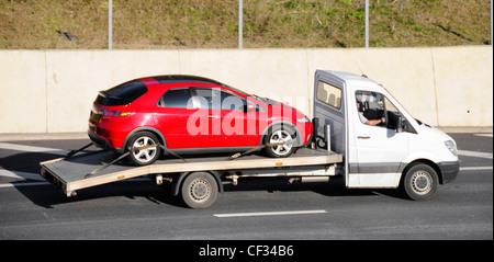 Weiß nicht markierten pickup Lkw Lkw Auto transporter mit roten Auto fahren entlang der Autobahn M25 Essex England - Stockfoto