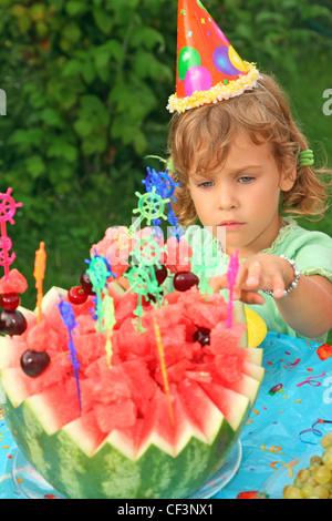 kleines Mädchen in GAP isst Obst im Garten, happy birthday - Stockfoto