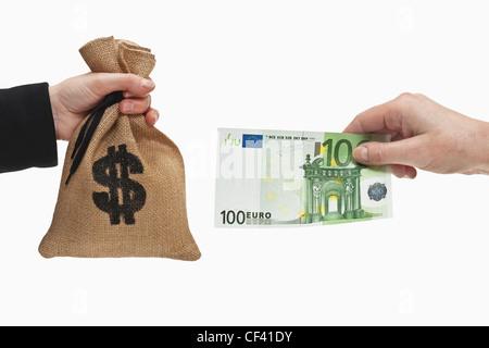 Ein 100 Euro-Schein ist in der Hand gehalten. Auf der anderen Seite ist ein Geldbeutel mit einem US-Dollar-Währung - Stockfoto