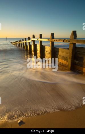 Wellen um hölzerne Küstenschutzes an der Strandpromenade Dawlish bei Tagesanbruch. - Stockfoto