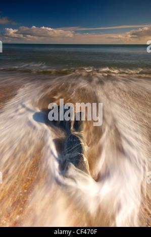 Wellen um einen Felsen am Hallsands Strand an der Küste von South Hams. - Stockfoto