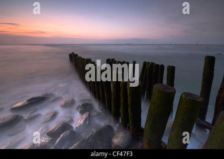 Wellen um hölzerne Küstenschutzes bei Lynmouth auf der Nord-Devon Küste bei Sonnenuntergang. - Stockfoto