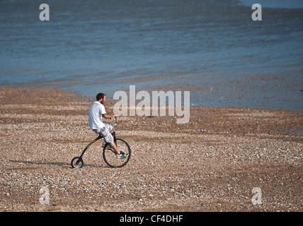 Mann auf Hochrad am Strand entlang der Uferlinie - Stockfoto