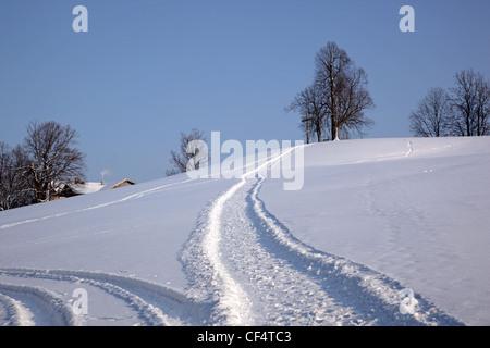 Verschneiten Strecke führt zu Hügel mit hölzernen Kreuz Buchberg in der Nähe von Bad Tölz Bayern Deutschland Europa - Stockfoto