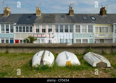Bunte Terrassen direkt am Meer Ferienhäuser mit drei umgestürzten Ruderboote im Vordergrund. - Stockfoto