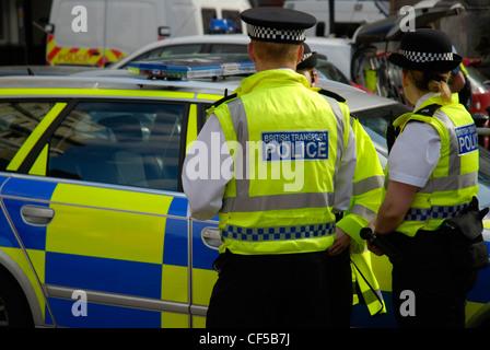 Britischen Transport Polizisten in gelben Jacken stehen neben einem Polizeiauto in Westminster. - Stockfoto