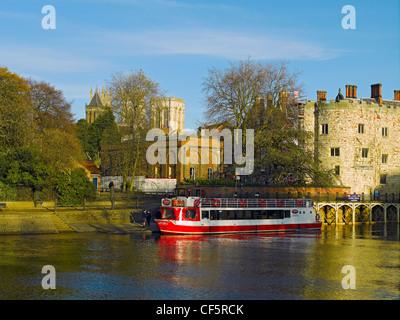 Ausflugsschiff vor Anker am Fluss Ouse im Lendal Tower mit York Minster im Hintergrund. - Stockfoto