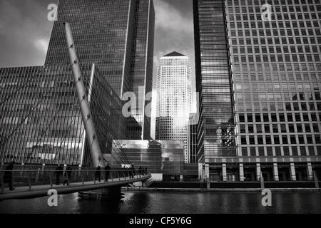 Blick über eine Fußgängerbrücke über die West India Millwall Docks gegenüber den Wolkenkratzern in Canary Wharf, - Stockfoto