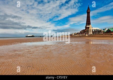Ein Blick über den Sandstrand in Richtung Blackpool Tower und North Pier an einem Sommertag. - Stockfoto