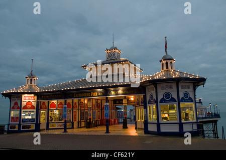 Ein Blick auf den Eingang zum Eastbourne Pier in der Abenddämmerung. - Stockfoto