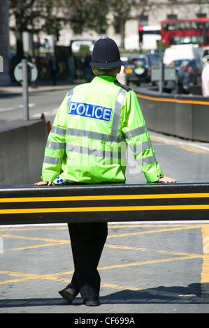 Ein Metropolitan Police Constable eine hohe Sichtbarkeit Uniform und Helm tragen. Die Metropolitan Police ist Londons - Stockfoto