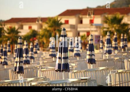 Liegestühle und Strand Sonnenschirme ordentlich gebaut Reihen am Strand morgens neben Hütten, flacher Schärfentiefe - Stockfoto