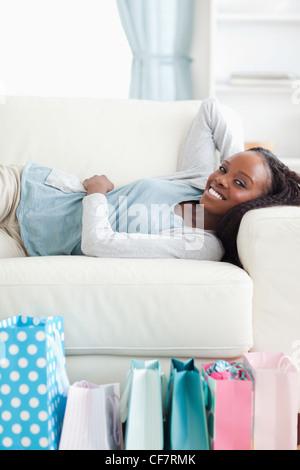 Frau liegend auf Sofa nach dem Einkauf - Stockfoto