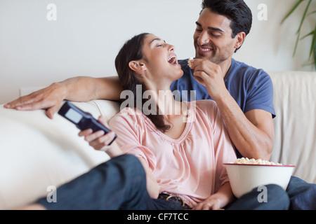 Verspieltes paar vor dem Fernseher während des Essens popcorn - Stockfoto