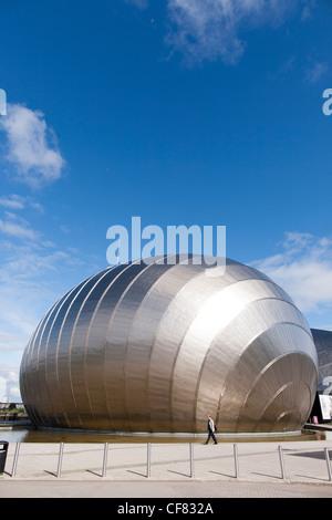 Eine Frau geht vorbei an der Glasgow Science Centre, ein Gebäude im Stil moderner Architektur in Schottland entwickelt. - Stockfoto