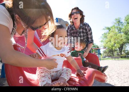 Japanische Mutter und amerikanische Mutter, die ein Playdate mit ihren Babys in einem Park. - Stockfoto