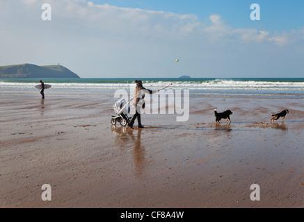 Frau wirft einen Ball für ihre Hunde an Polzeath Strand in Cornwall, Großbritannien - Stockfoto