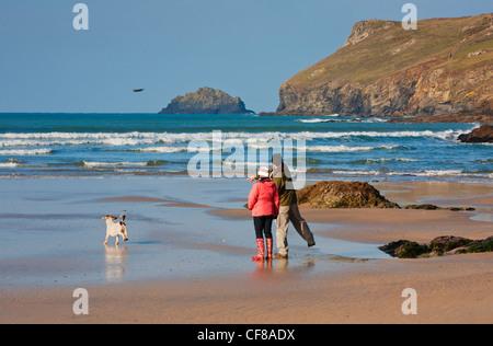 Paare, die mit ihrem Hund an Polzeath Strand in Cornwall. - Stockfoto