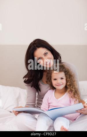 Mutter und Tochter ein Buch auf dem Bett - Stockfoto