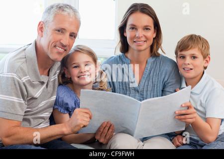 Glückliche Familie zusammen ein Buch lesen Stockfoto