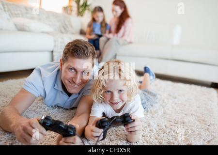 Vater und Sohn im Wohnzimmer spielen von Videospielen - Stockfoto