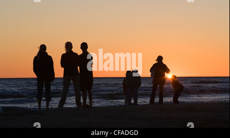 Eine Familie wacht den Sonnenuntergang über Lake Huron in Sauble Beach, Ontario, Kanada. - Stockfoto