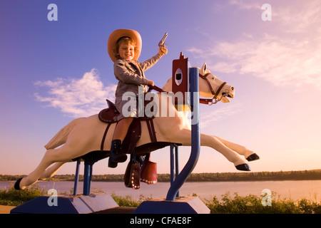 5 Jahre altes Mädchen in westlicher Kleidung sitzt auf Pony Fahrgeschäft, Kanada gekleidet. - Stockfoto