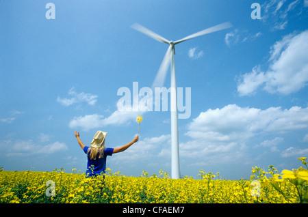 15 Jahre altes Mädchen mit Windrad Windkraftanlage in Raps Feld, nahe St. Leon, Manitoba, Kanada anzeigen. - Stockfoto