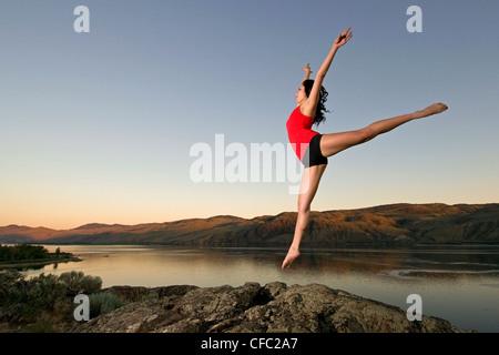 Eine schöne junge Frauen Praktiken Tanz während über Kamloops See bei Sonnenuntergang, Kamloops, Britisch-Kolumbien, Kanada