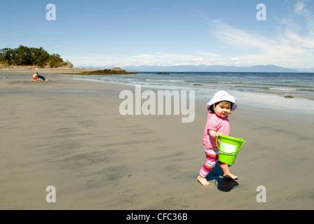 Kleinkind spielt am Strand von Pipers Lagune, Nanaimo, BC, Kanada. - Stockfoto