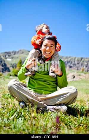 eine Frau lächelt wie sie sitzt Schneidersitz in einer Almwiese mit Wildblumen eine Buddha-Pose zu tun. Ihr Sohn, - Stockfoto