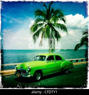 Leuchtend grüne amerikanische Oldtimer parkte vor einer Palme mit dem Ozean hinter Punta Gorda, Cienfuegos, Kuba, - Stockfoto